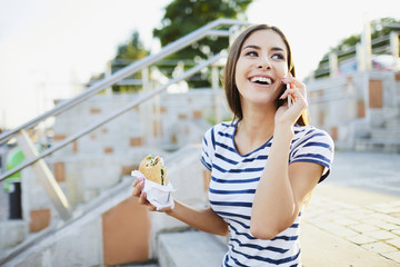 Young woman talking on phone and eating bagel in the city