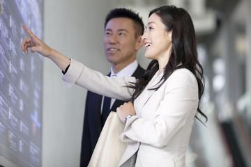 掲示板を見るビジネスマンとビジネスウーマン