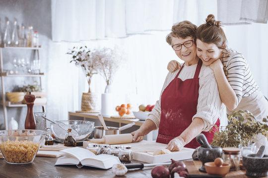 Granddaughter hugging grandmother in the kitchen