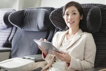 機内でタブレットPCを持つビジネスウーマン