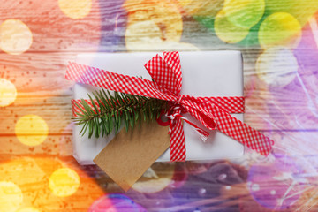 Holiday gift box. Christmas present with tag at white wooden table with bokeh effect