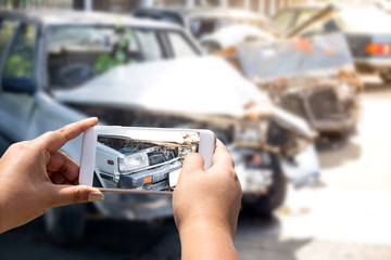woman is photographing an accident car using a camera from a mobile phone.
