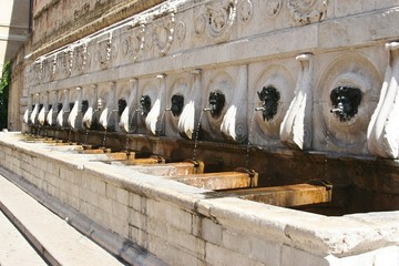 bronze faces historical fountain in Ancona, Marche, Italy