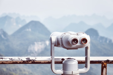 Vintage toned picture of tourist binoculars pointing at karst formations around Guilin. It is one of China most popular tourist destinations. Selective focus.