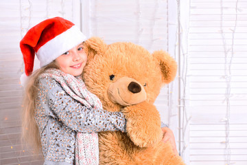 Miss Santa in hat hugs bear. Girl with smiling face