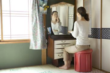 化粧台の前に座り化粧をする50代女性