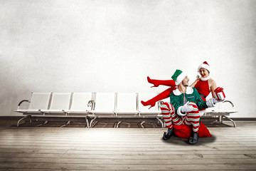 Two Christmas elves in the waiting room. a large wooden floor, white chairs and a white wall with space for your inscription. Christmas advertising background.