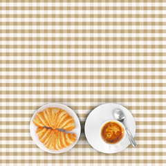 Brown squared tablecloth with cappuccino and croissant