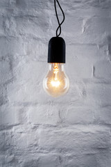 Light bulb on white brick wall background