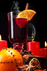 Glass of christmas hot mulled wine on wooden table with species ,oranges and red candles against black background.Closeup.Slective focus
