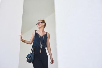 Portrait of beautiful stylish Caucasian smiling blonde woman standing outdoors.
