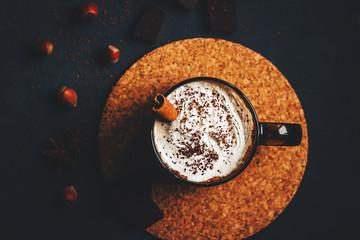 hot chocolate with cream in a dark mug on a black background