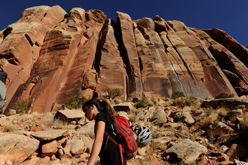 A rock climber walks below a rock facing near the Indian Creek area of Bears Ears, New Mexico