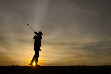 silhouette asian golfer playing golf during beautiful sunset
