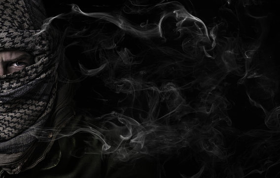 face of a bandit in military uniform on a black background with smoke