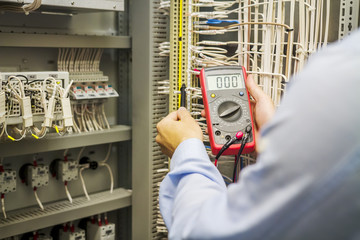 Engineer electrician with multimeter in hands at electric automation box panel. Service engineer tests circuit of industrial equipment