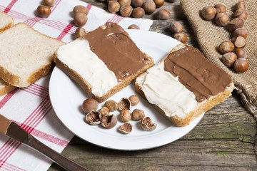 bread slice with nutella chocolated and vanilla cream on wooden table with hazelnuts