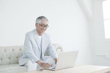 ソファに座りノートパソコンを使う中高年男性