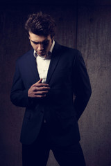 Handsome male model posing and looking down in fashion suit and white style shirt on dark shadow background. Closeup portrait.
