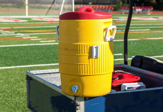 Yellow water cooler on a blue cart with soccer net in background
