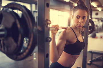 Young female doing exercise with barbell