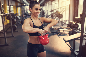 Woman practicing arm muscles with kettle bell weight in gym