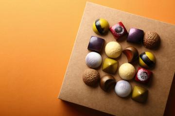 chocolate candy on box on orange background