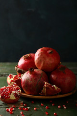 Fresh pomegranates on dark background