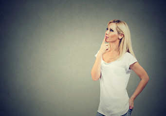 Side profile of a happy woman thinking with finger on chin gesture looking up
