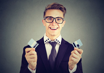 Debt free business man holding a credit card cut in two pieces