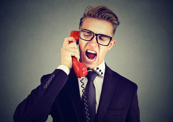 Angry young business man yelling on the phone