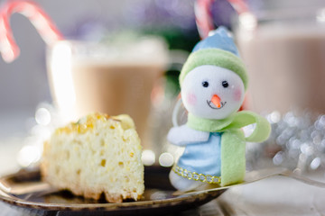Winter snowman sitting near the plate with christmas pie