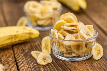 Portion of Dried Banana Chips on wooden background, selective focus