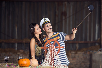 Young couple costumed as sailor and indian woman taking selfie