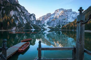 Idyllischer Bergsee mit Anlegesteg und Booten vor malerischer Felslandschaft