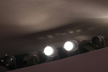 Two bright spotlights shine under the ceiling in the concert hall.