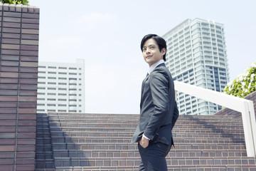 階段を上がるスーツ姿の20代の日本人男性