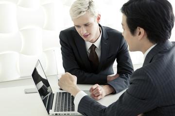 パソコンを使うスーツ姿の20代の外国人男性と日本人男性