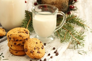 Chocolate chip cookies and glass of milk on festive Xmas background, selective focus