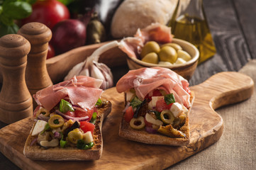 Bruschetta with vegetables and ham, italian style cuisine.