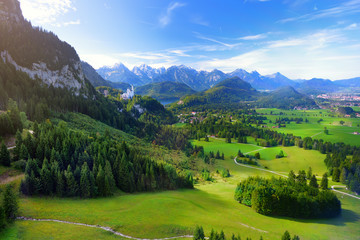 Fototapete - Famous Neuschwanstein Castle visible in the distance, located on a rugged hill above the village of Hohenschwangau in southwest Bavaria, Germany