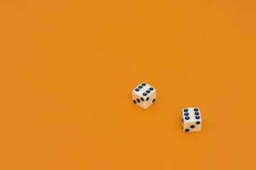 Isolated white dice on a orange background