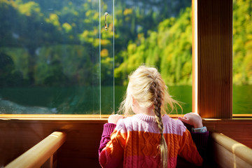 Fototapete - Little girl enjoying a view of deep green waters of Konigssee while traveling by electric boat