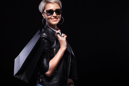 Black friday holiday. Happy blonde woman at shopping holding bags isolated on black background.. Copy space for sale.