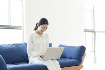 ソファーでパソコンを使う20代女性