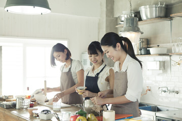 Three young women cooking