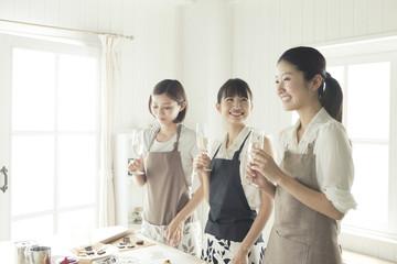飲みながらお菓子作りをする20代女性3人