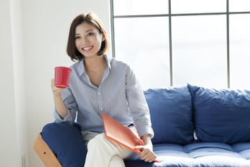 ソファーでコップを持つ20代女性
