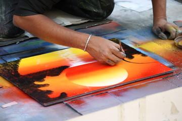street art, street painter paints sunset on canvas