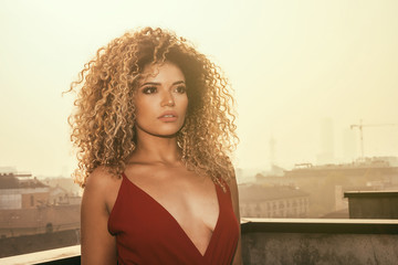 Woman portrait with gorgeous curly hair standing on rooftop